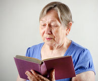 Elderly  woman with book Stock Photos