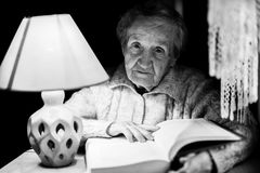 An elderly woman with a book. Stock Images