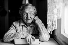 An elderly woman with a book in hand. Sitting at a table near the window Stock Photos