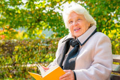 Elderly woman with a book resting Royalty Free Stock Photography