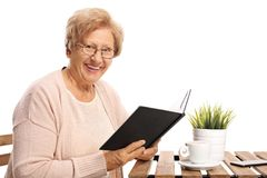 Elderly woman with a book sitting at a coffee table and looking stock image