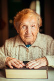 Elderly woman with book sitting at table. Royalty Free Stock Photo