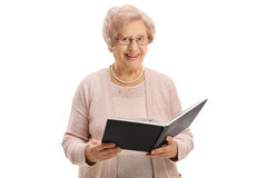Elderly woman with a book smiling Stock Images