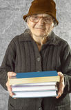 Elderly woman with books. Elderly woman holding stack of books royalty free stock images