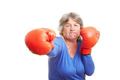 Elderly woman with boxing gloves. Elderly woman fighting with red boxing gloves royalty free stock photo