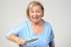Elderly woman brandishing a kitchen knife Royalty Free Stock Images