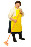 Elderly woman with broom. Full length of elderly woman with yellow apron cleaning house with broom isolated on white background royalty free stock image
