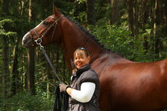 Elderly woman and brown horse portrait in the forest. Happy elderly caucasian woman and bay latvian horse portrait in forest Stock Photo