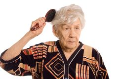 The elderly woman brushes hair Royalty Free Stock Photos