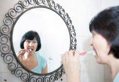 Elderly woman brushing her teeth royalty free stock image