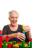Elderly woman building a brick Stock Photography