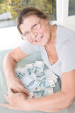 An elderly woman with a bunch of Russian money and savings book. Studio photography at the table on a light background Royalty Free Stock Photography