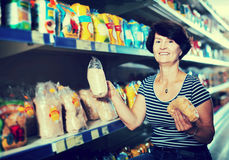 Elderly woman buying groats. Portrait of an aged woman buying a groats at the grocery shop Royalty Free Stock Image