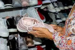 An elderly woman buys sneakers in a boutique. The choice of sports shoes in the store stock photography