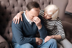 Elderly woman calming down her depressed husband. Please calm down. Elderly women is sitting and embracing her husband in depression at home stock image
