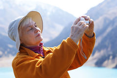 An elderly woman with a camera. In the mountains Royalty Free Stock Images