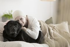 Woman with cancer hugging dog. Elderly woman with cancer hugging dog while lying on sofa at home stock photography