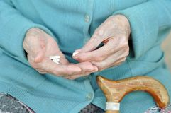 An elderly woman with a cane holding a pill on the street. 90 years. Health. concept illness and healthcare stock images
