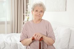 Elderly woman with cane sitting on bed Stock Image