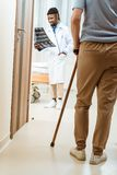 elderly woman with cane walking into a hospital room with young doctor holding royalty free stock photo