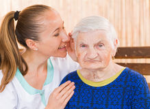 Elderly woman with caregiver Stock Images