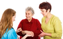 Elderly woman with carer and the young doctor. Elderly women with carer visit the young female doctor Royalty Free Stock Photo