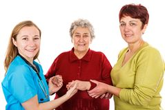 Elderly woman with carer and the young doctor. Elderly women with carer visit the young female doctor Royalty Free Stock Photos
