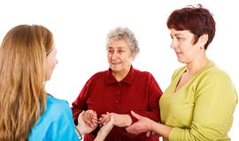Elderly woman with carer and the young doctor. Elderly women with carer visit the young female doctor Stock Image