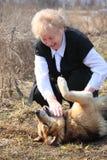 Elderly woman caresses dog Royalty Free Stock Photography
