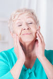 Elderly woman caring about her face Royalty Free Stock Image