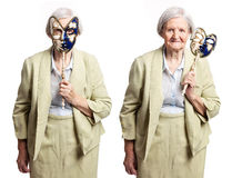 Elderly woman with carnival mask standing on white Stock Photo
