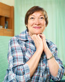 Elderly woman in casual clothes sitting on couch Royalty Free Stock Photos
