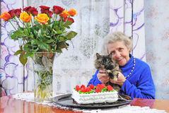 Elderly woman with cat. Sit on the table Stock Photos