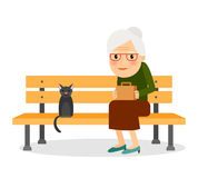 Elderly woman and cat sitting on park bench Stock Photo