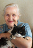 Elderly woman with cat. Smiling happy elderly woman with her cat. Selective focus on a cat Stock Photo