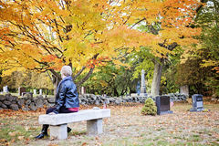 Elderly woman in cemetery. A back view of an elderly woman sitting on a bench in a cemetery in Autumn royalty free stock photos