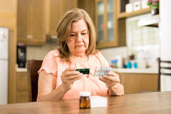 Elderly woman checking her medicines expiration date. Good looking senior adult woman looking at her pills` expiration date sitting in the kitchen Royalty Free Stock Photo