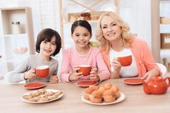 Elderly woman and cheerful grandson and granddaughter drink tea from red mugs in kitchen. Elderly women and cheerful grandson and granddaughter drink tea from stock images