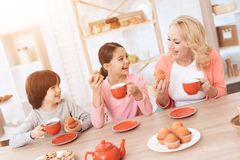 Elderly woman with cheerful grandson and granddaughter eating cookies and drinking tea in red mugs at kitchen. Stock Image