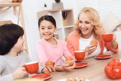 Elderly woman with cheerful grandson and granddaughter eating cookies and drinking tea in red mugs at kitchen. Elderly women with cheerful grandson and stock photo