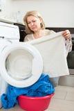 Elderly woman cheking white clothes Stock Image