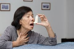 Elderly woman choking and holding an asthma spray. At home Stock Image