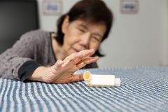 Elderly woman choking and holding an asthma spray. At home Royalty Free Stock Photography