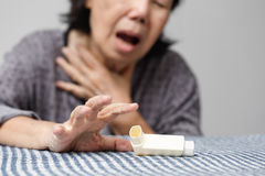 Elderly woman choking and holding an asthma spray. At home Stock Photo