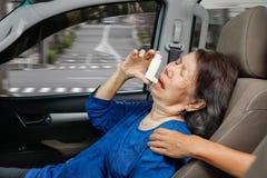 Elderly woman holding an asthma spray inside car Stock Photos