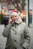 Elderly woman at Chrismas market with smartphone Stock Image
