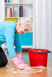 Elderly woman cleaning floor. At home, kneeling stock photography