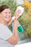 An elderly woman cleaning a window. Stock Photo