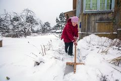 Elderly woman cleans snow near the his rural house. Help. Royalty Free Stock Photography