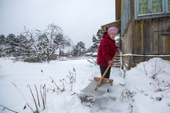 Elderly woman cleans snow near his rural house. Help. Royalty Free Stock Photography